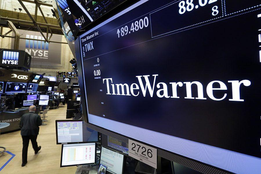 A trader walks by the post that handles Time Warner on the floor of the New York Stock Exchange, Monday, Oct. 24, 2016. AT&Ts $85.4 billion purchase of Time Warner represents a new bet on synergy between companies that distribute information and entertainment to consumers and those that produce it. (AP Photo/Richard Drew)