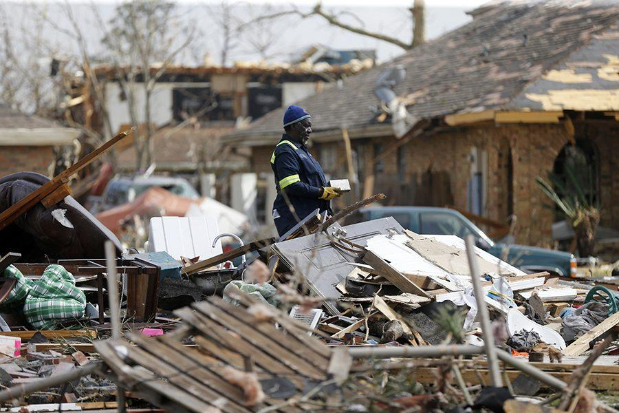 Willie Anderson tries to salvage possessions from his daughters destroyed home, in the aftermath of Tuesdays tornado that tore through the New Orleans East section of New Orleans, Wednesday, Feb. 8, 2017. (AP Photo/Gerald Herbert)