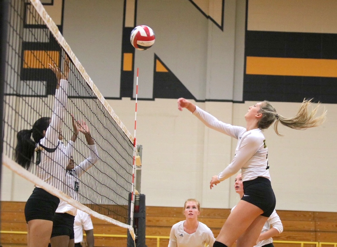 Senior Sydney Moxcey spikes the ball over the net in Klein Oak's victory over Cy Falls, Tuesday, August 7, 2018