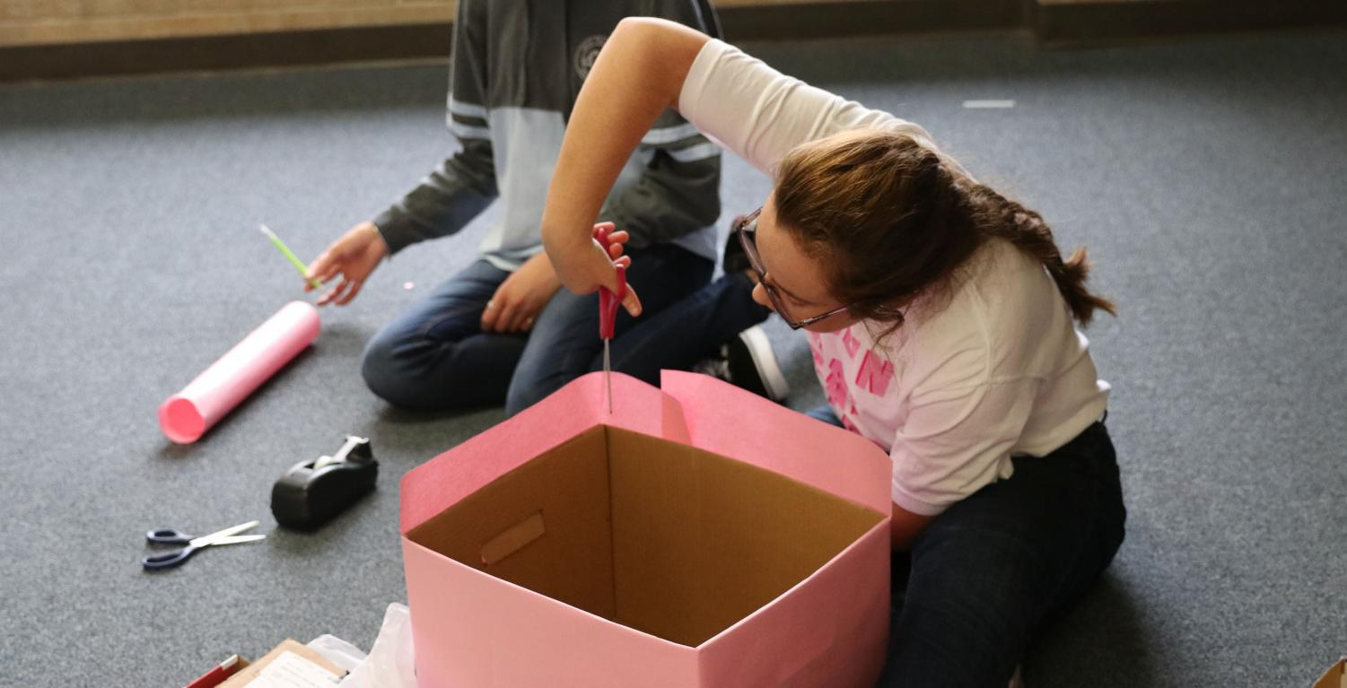 Sophomore chair member Gaus- Schmidt helps create donation boxes.