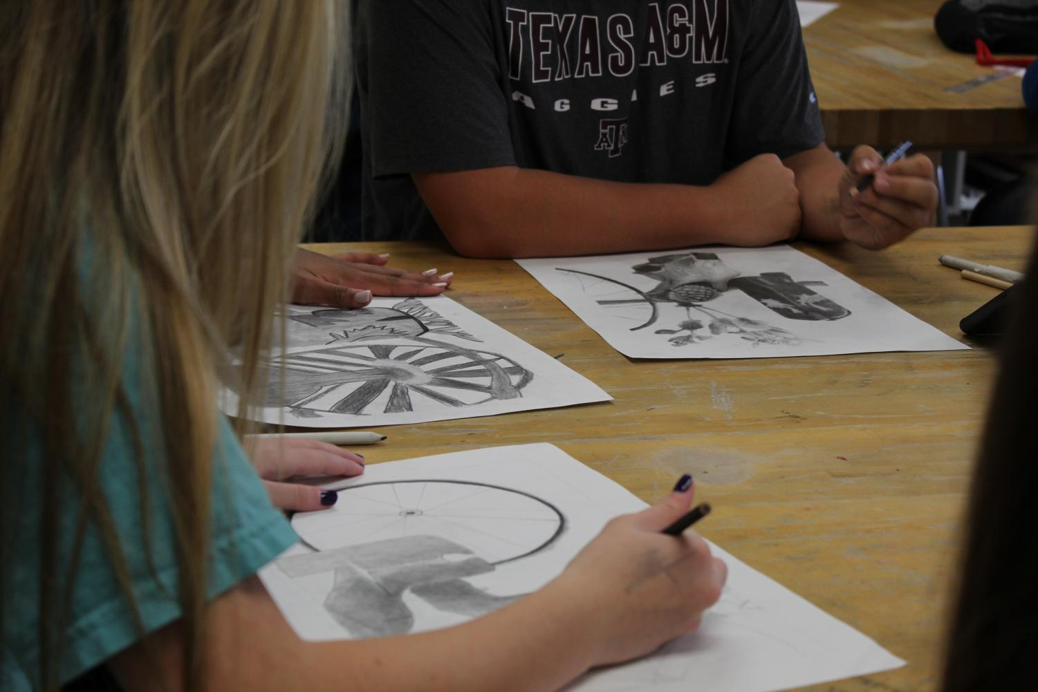 Art students add to the final touches of their rodeo sketches.