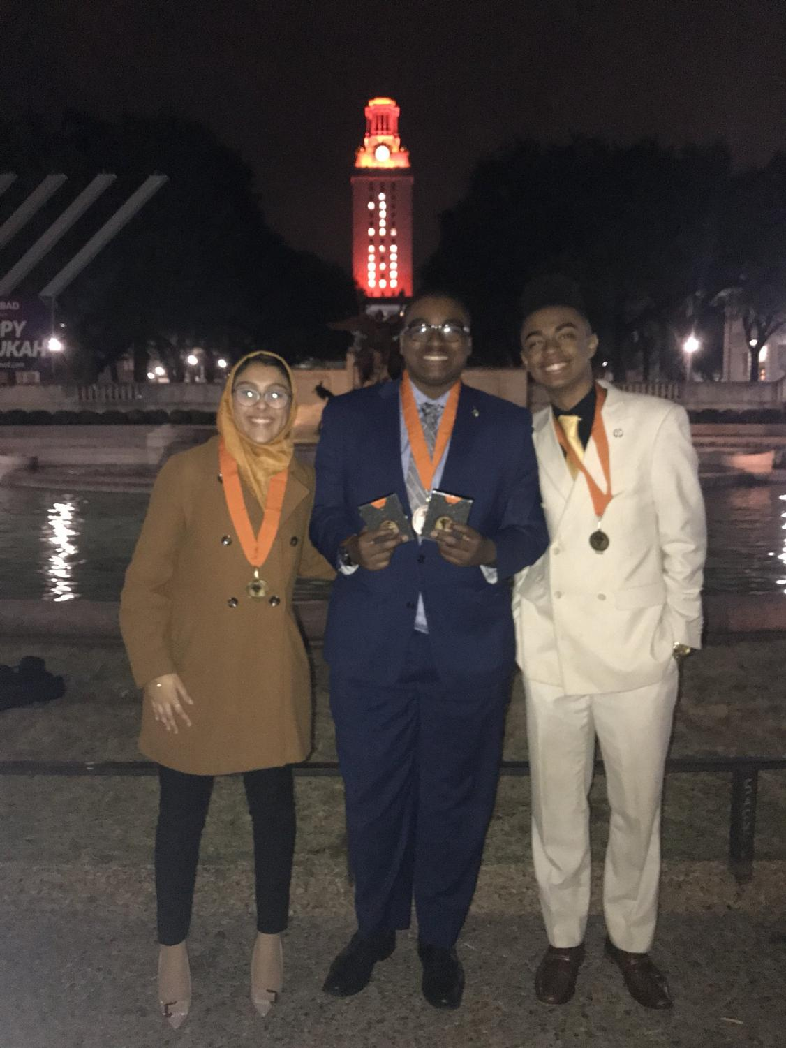 Award winning seniors Noor Iqbal, Marc Wynne and Jeremiah Williams stand in front of the UT tower with their trophies and medals.