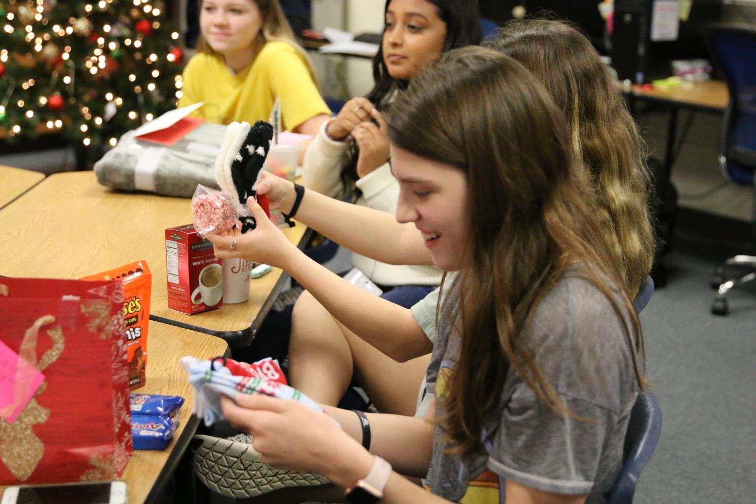 Secret Santa participants are filled with joy while they open the gifts they received.