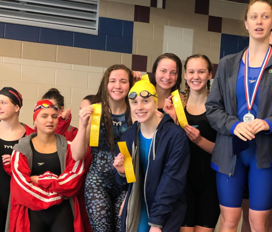 The girls 200 Medley relay stands on the podium after placing 4th. Zoe Uehlinger, Taryn Kooyers, Annie LeBlanc and Avery Fuhr holding up their ribbons.