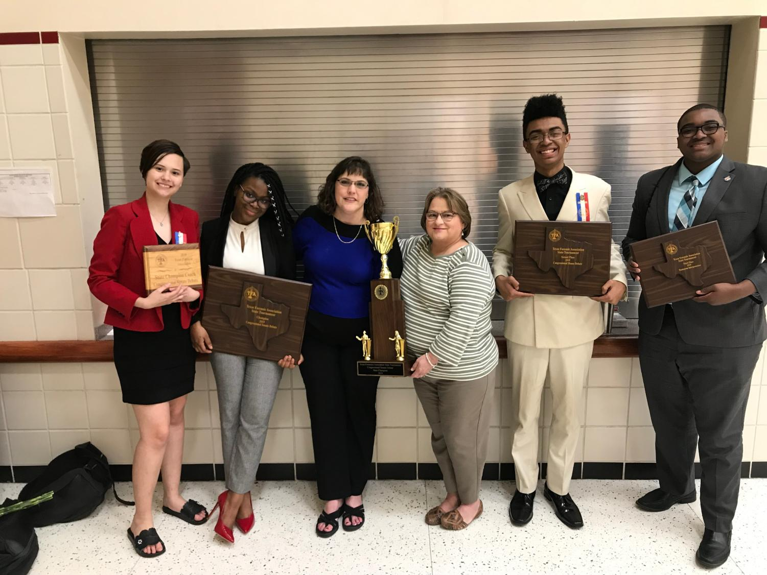 Winning several top awards at the Texas Forensic Association State Tournament, junior Skylar Dixon-Englert, junior Ayo Adereti, Coach Angie Richard, Coach Debby Carpenter, senior Jeremiah Williams and senior Marc Wynne display the championship hardware.