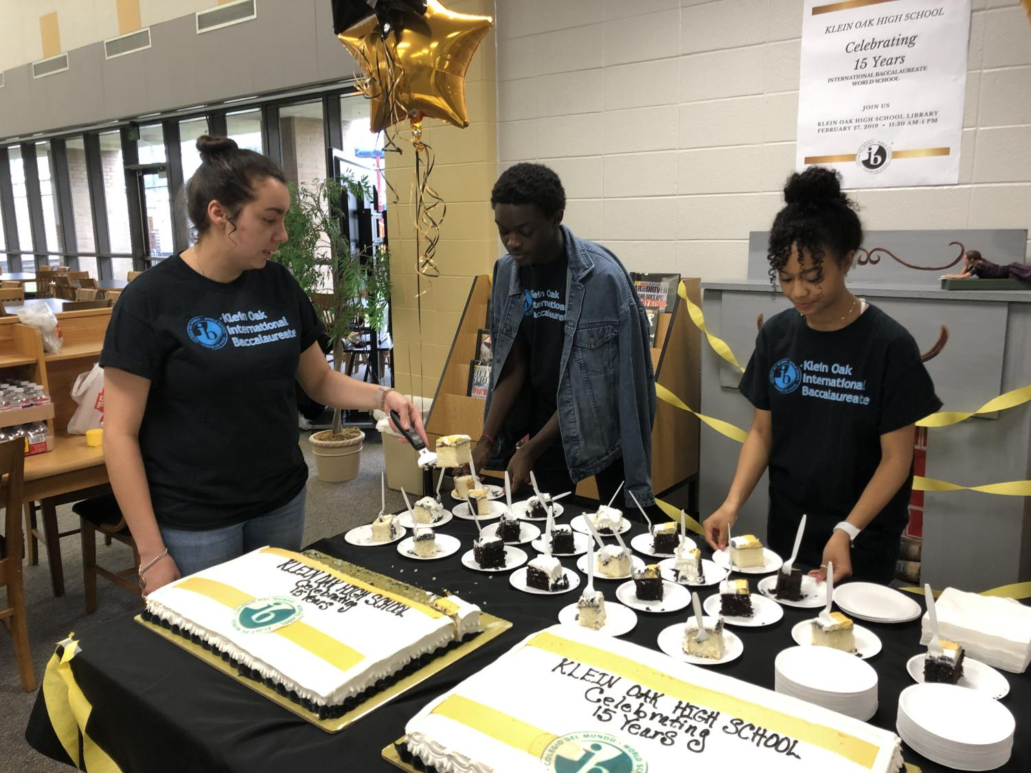 Franchesca Esquivel, Kwame Ofori, and Tatyana Ranson serve cake during the IB Anniversary Celebration in the library.