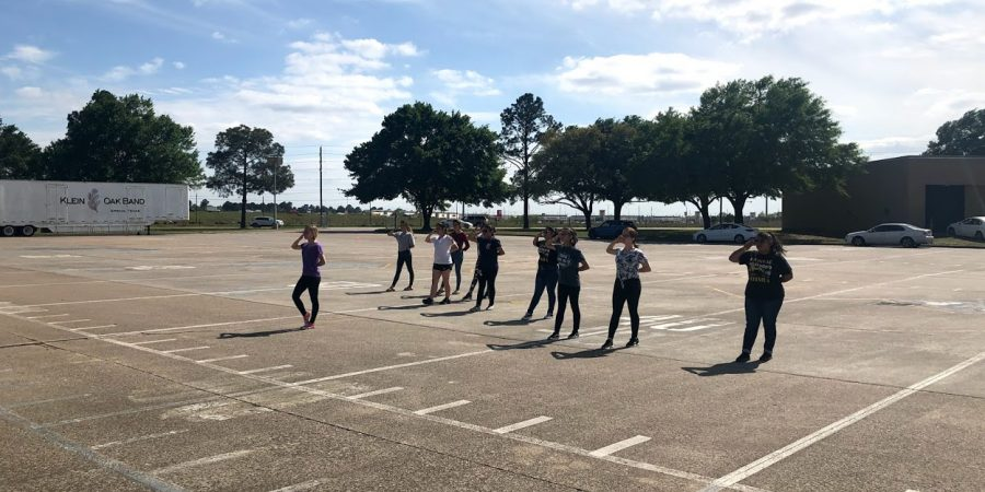 The Golden spades perfect their sequences in the band parking lot after school.