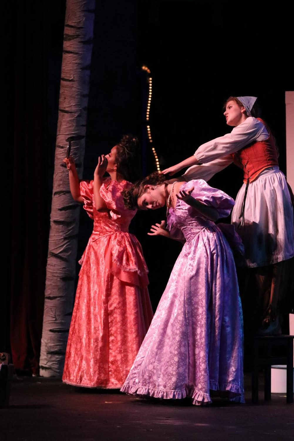Cinderella, played by senior Abigail Reed, yanks the hair of her step-sister's, played by senior Lily Tungol.