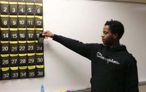 Senor David Oderinde  puts his phone in 'phone jail' for the  duration of Brad Rice's math class. The cell phone policy at Klein Oak differs from teachers to teacher, but the thought about cell phone are the same: when they become a distraction, they are to be put away.