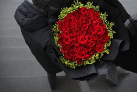 A bouquet of roses is exchanged in a Beijing market between seller and customer on Valentine