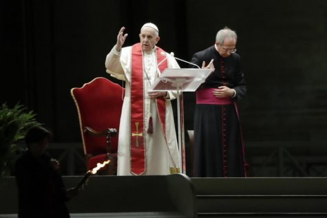Pope Francis is flanked by Mons. Guido Marini as he delivers his blessing during the Via Crucis – or Way of the Cross – ceremony in front of St. Peter