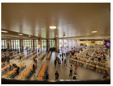 "Students search through tables with for an open spot without a brightly colored ""X"" to sit in the commons."