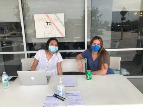 Sitting at the registration booths, seniors Lucia MoraUrbina and Caitlyn Nguyen anticipate eligible voters to pick up available registration forms outside the Nails of America Salon.