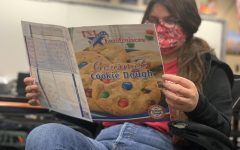 Senior Natalia Bond browses through the Cookie Dough Fundraiser product brochures in a classroom. Seniors are encouraged but not required to participate in the money-making event for prom.