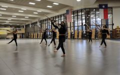 Practicing the varsity rifles warm up exercises, Winter Guard captain Danielle Fontenot concentrates on technique and skill set. The guard will present their performance titled The Introduction of Color at the first contest of the season.