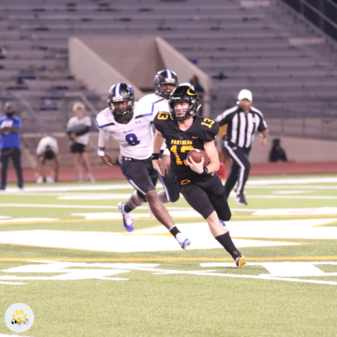 Looking to gain more yardage, senior quarterback Tyler Jackson protects the ball. Oak went on to defeat Dekaney, 41-6.